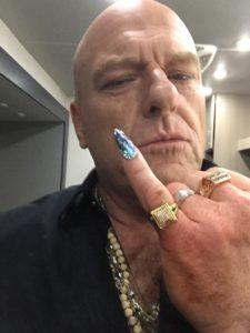 Uncle Daddy dans la série Claws qui porte à l'auriculaire une prothèse ongulaire